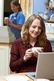 Женщина в кофейне используя портативный компьютер Стоковое Изображение