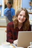 Женщина в кофейне используя портативный компьютер Стоковая Фотография