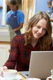 Женщина в кофейне используя портативный компьютер Стоковое фото RF
