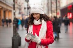 Женщина в красной крышке пальто и шерстей и перчатки с smartphone в Хане Стоковое Фото