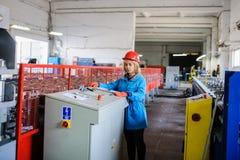 Женщина в красной работе шлема безопасности как промышленный работник Стоковые Изображения RF