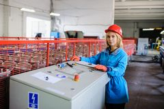 Женщина в красной работе шлема безопасности как промышленный работник Стоковая Фотография
