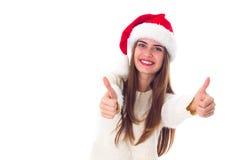 Женщина в красной шляпе рождества показывая большие пальцы руки вверх Стоковые Фотографии RF