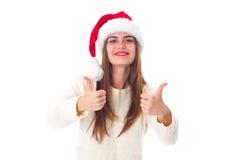 Женщина в красной шляпе рождества показывая большие пальцы руки вверх Стоковая Фотография RF