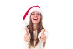 Женщина в красной шляпе рождества показывая большие пальцы руки вверх Стоковые Изображения
