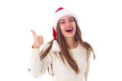 Женщина в красной шляпе рождества показывая большой палец руки вверх Стоковое фото RF