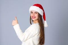 Женщина в красной шляпе рождества показывая большой палец руки вверх Стоковая Фотография