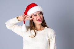 Женщина в красной шляпе рождества показывая мир Стоковые Изображения RF