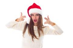 Женщина в красной шляпе рождества показывая пистолеты Стоковая Фотография RF