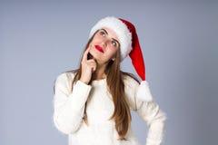 Женщина в красной шляпе рождества смотря вверх Стоковое фото RF