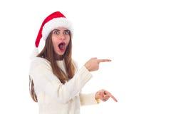 Женщина в красной шляпе рождества указывая на что-то Стоковые Изображения