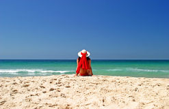 Женщина в красном бикини и шлеме сидя в мире на красивейшем солнечном пляже. Стоковая Фотография