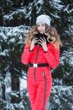 Женщина в красном комбинезоне в зиме стоковое фото rf