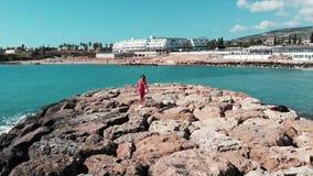 Женщина в красном красивом платье идя самостоятельно на скалистую пристань на заливе Кипре коралла с гостиницой и пляж на предпос сток-видео