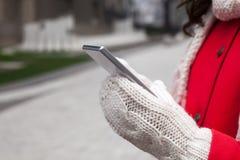 Женщина в красном пальто с smartphone в руках идя через cit Стоковые Изображения