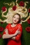 Женщина в красном платье кладя на траву Стоковое Изображение RF