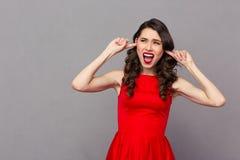 Женщина в красном платье покрывая ее уши с пальцами Стоковая Фотография RF