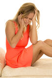 Женщина в красном платье сидит на белой софе унылой стоковое фото rf