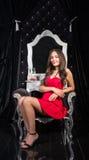 Женщина в красном платье сидя в стуле перед одевать плату Стоковые Изображения RF