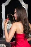 Женщина в красном платье сидя в стуле перед одевать плату Стоковые Фотографии RF