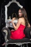 Женщина в красном платье сидя в стуле перед одевать плату Стоковое Фото