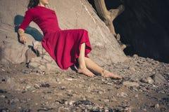 Женщина в красном платье сидя пещерой на пляже Стоковые Изображения RF