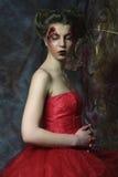 Женщина в красном платье Фантастический стиль причёсок и составляет стоковое фото