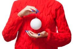 Женщина в красном свитере держит шарик рождества белый на белой предпосылке Стоковые Фотографии RF
