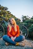 Женщина в красном свитере на предпосылке велосипеда и леса Стоковая Фотография