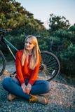 Женщина в красном свитере на предпосылке велосипеда и леса Стоковые Фото