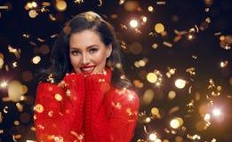 Женщина в красном свитере на черной предпосылке стоковые фото