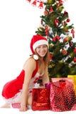 Женщина в красном усаживании под рождественской елкой с подарками Стоковые Изображения