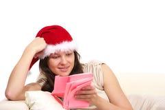 Женщина в красном чтении шлема рождества Стоковое фото RF