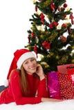 Женщина в красный лежать под рождественской елкой с подарками Стоковое Изображение
