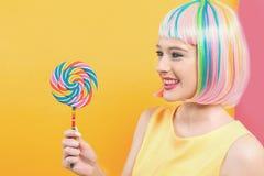Женщина в красочном парике с леденцом на палочке стоковое фото