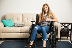 Женщина в кресло-коляске используя smartphone Стоковое фото RF