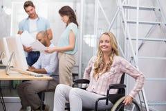 Женщина в кресло-коляске усмехаясь на камере с командой за ей стоковое изображение