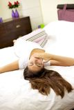 Женщина в кровати кладя утомлянный зевать Стоковое Фото