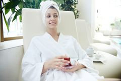 Женщина в купальном халате ослабляя бассейном в КУРОРТЕ стоковые изображения