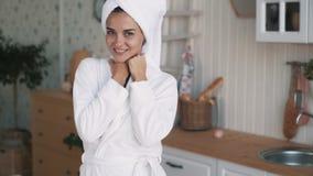 Женщина в купальном халате, с полотенцем на главных взглядах в камеру, улыбки, замедленное движение акции видеоматериалы