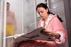 Женщина в купальном халате читая газету и ждать ее boyfr Стоковые Фотографии RF