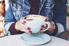Женщина в куртке джинсов держа чашку капучино в ее руках Стоковые Изображения RF