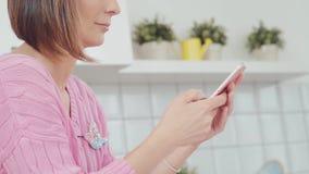 Женщина в кухне используя smartphone Профиль видеоматериал