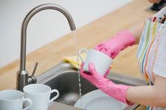 Женщина в кухне моет чашки и блюда r стоковое изображение rf