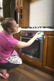 Женщина в кухне обтирая ткань на печи Стоковое фото RF