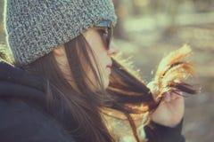 Женщина в лесе при солнечные очки играя с волосами Стоковые Фотографии RF