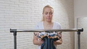 Женщина в магазине идет до вешалка с голубыми брюками джинсовой ткани, извлекает их все и принимает их сток-видео