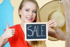 Женщина в магазине с знаком продажи стоковая фотография rf