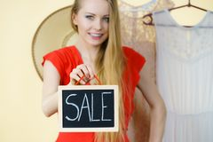 Женщина в магазине с знаком продажи стоковое изображение