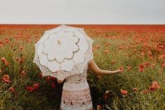 Женщина в маках field держать цветок и зонтик мака Арройо Стоковая Фотография